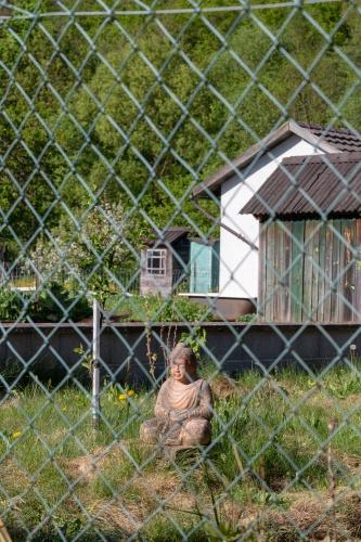 Buddha hinter bayerischem Gartenzaun
