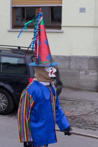 Maske mit Spitzhut und blauem Kittel